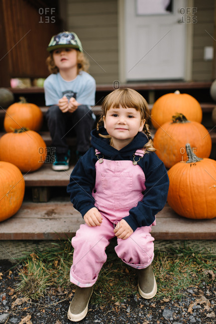 Two young siblings sitting on front steps with pumpkins