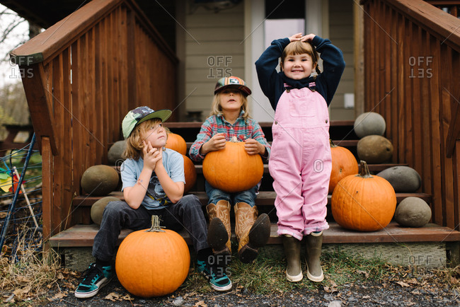 Three young children sitting on front steps with pumpkins