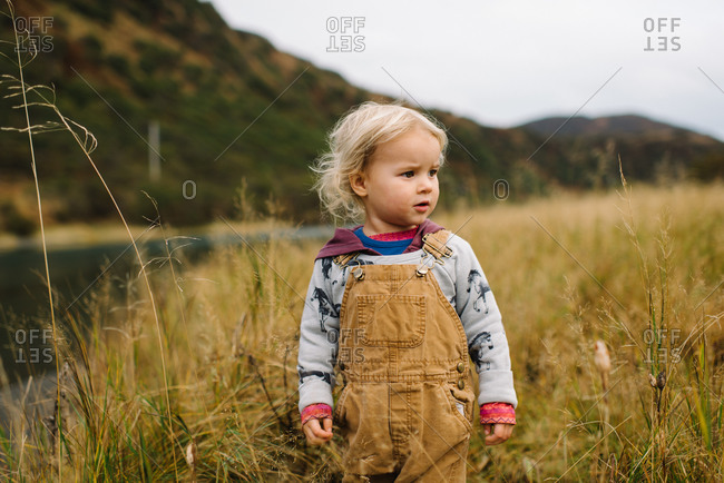 Cute toddler boy exploring tall grass by river