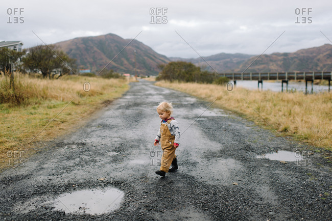 Toddler boy in boots and overalls walks on muddy dirt road in the country