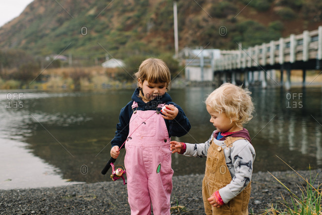Two young children in overalls with fishing pole on riverbank