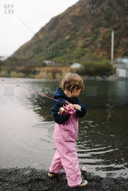 Young girl pulling in her fishing line on riverbank