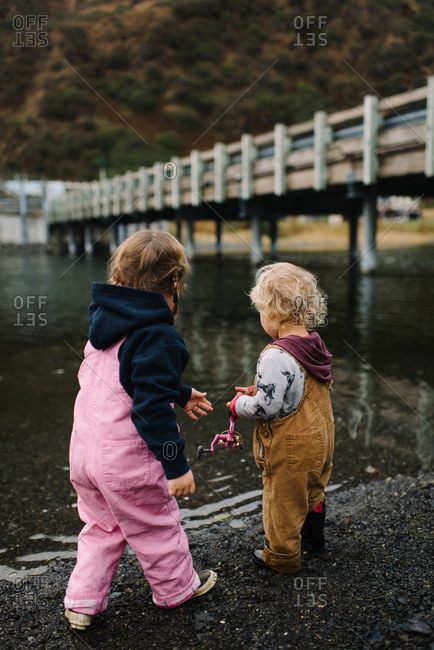 Two young siblings with fishing reel by river