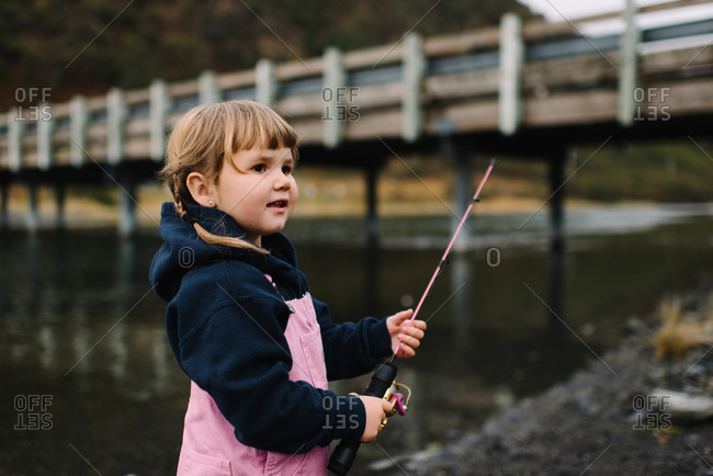 Portrait of a young girl in pink overalls fishing below bridge