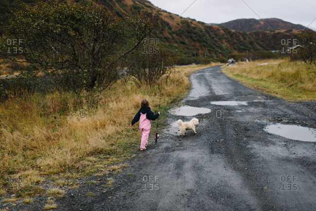 Young girl in pink overalls carries fishing pole down dirt road with dog