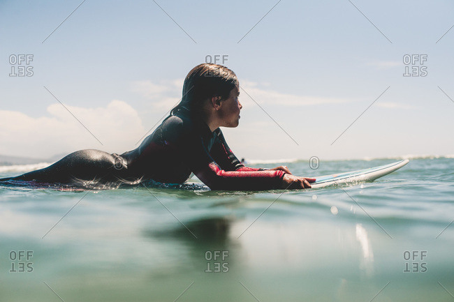 Boy in wetsuit floating on surfboard