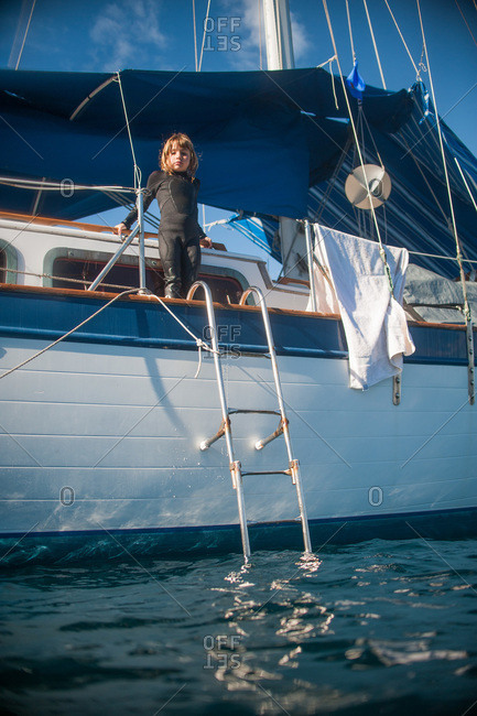 Girl in wetsuit standing on deck of a sailboat