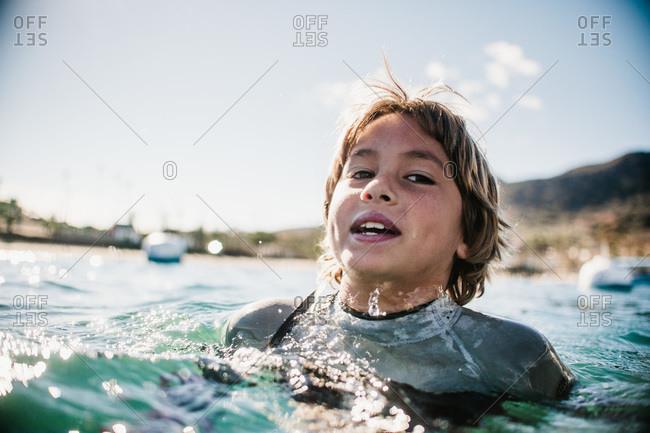 Boy in wetsuit treading water