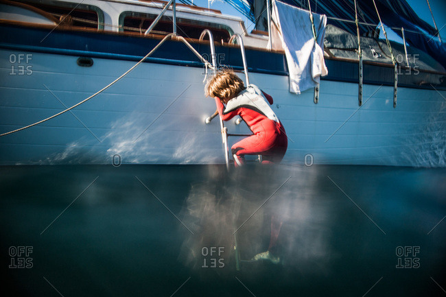 Boy in wetsuit climbing down ladder of a sailboat