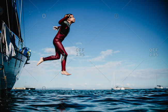 Boy in wetsuit jumping off sailboat