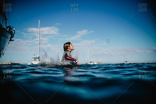 Boy in wetsuit jumping into water