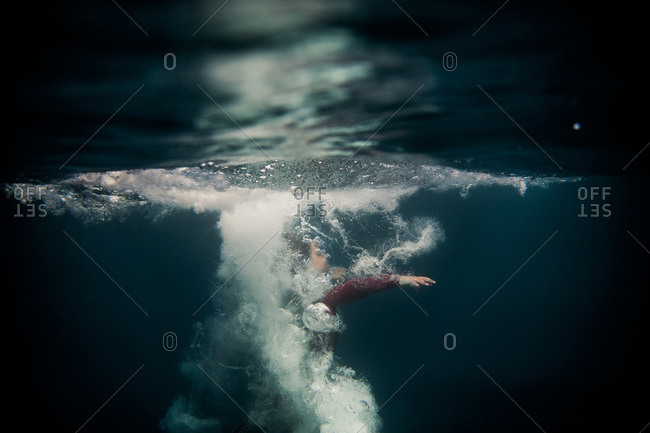 Boy in wetsuit diving underneath water surface