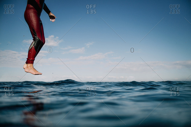 Boy diving into water with feet together