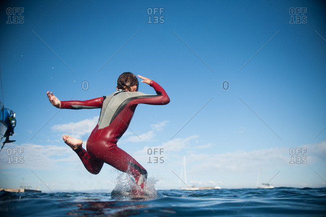 Boy diving, one foot into water