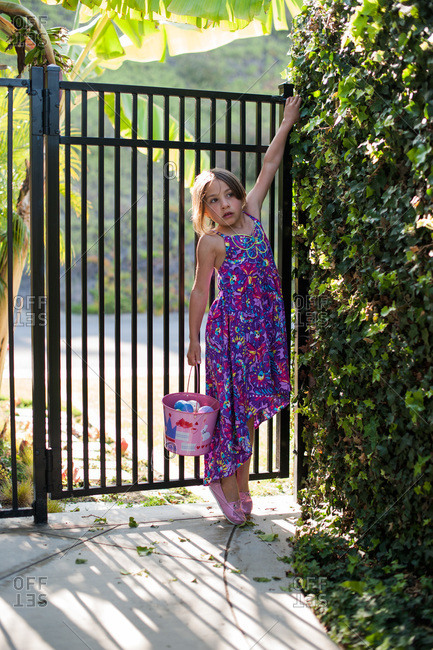 Girl standing on her tip toes to open a gate