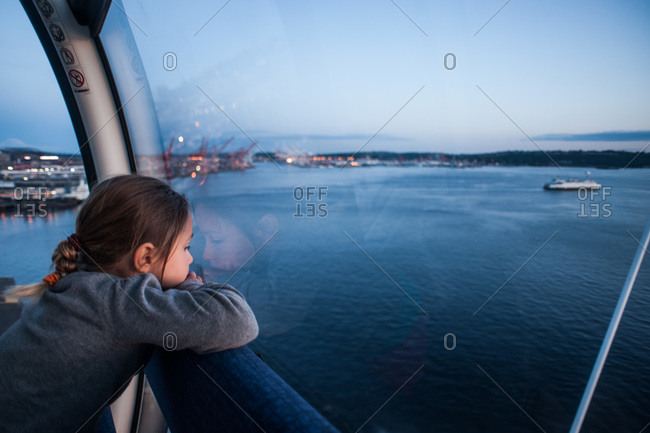 Little girl looking at the harbor from Ferris wheel on waterfront pier