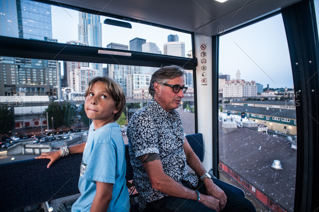 Father and son riding Ferris wheel on waterfront pier