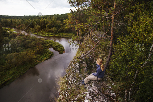 Woman overlooking river from rocky outcropping in forest