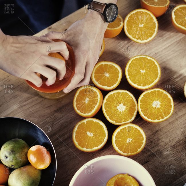 Overhead view of man juicing oranges by hand