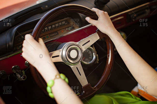 Woman's hands on steering wheel of vintage automobile