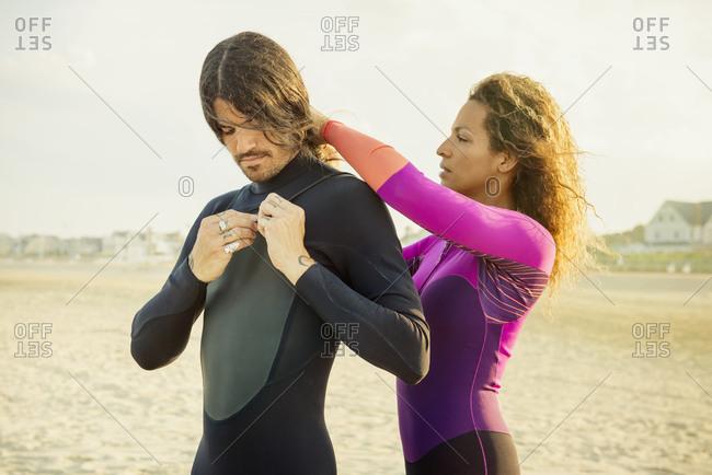 Woman unzipping her boyfriend's wetsuit on the beach