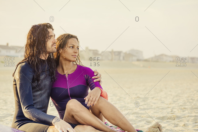 Couple cuddling on the beach at sunset
