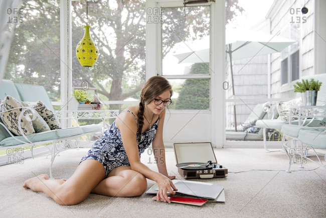 Teenage girl sitting on floor of screened porch listening to records