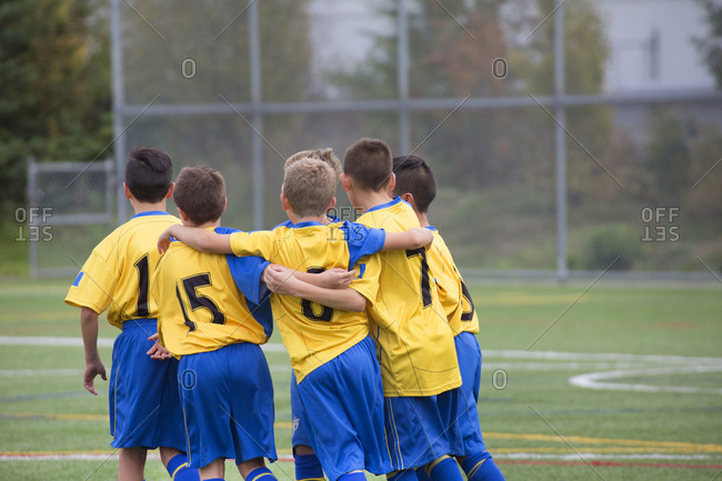 Back view of group of child teammates celebrating soccer goal