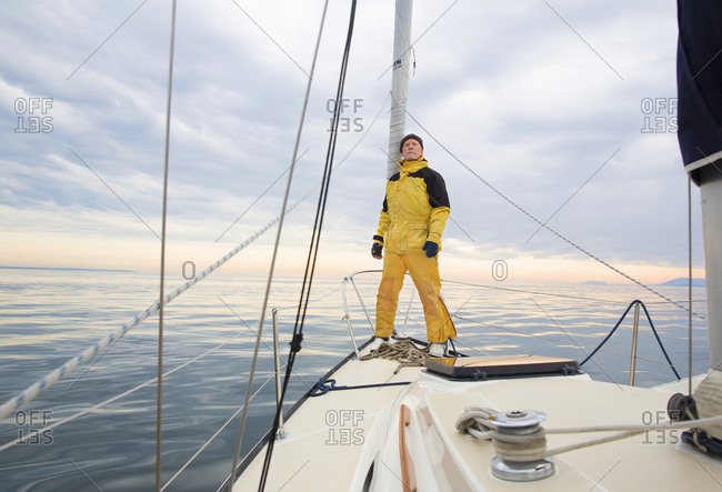 Senior man in yellow rain gear stands on deck of sailboat