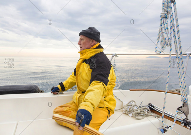 Senior man in yellow train gear with his hand on the till of his sailboat