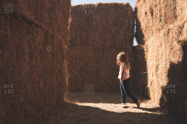 Girl walking through a hay bale maze