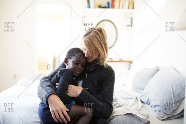 Caucasian mother holding her adopted African American son on her lap in bedroom