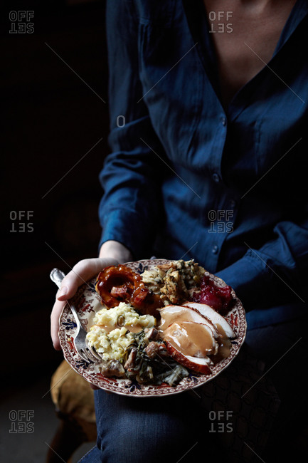 Woman with a plate of turkey, mashed potatoes and stuffing