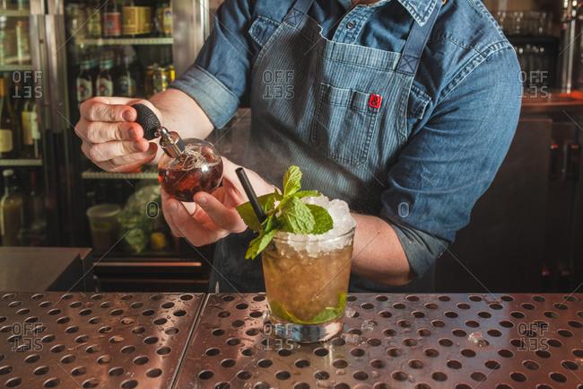 Bartender spritzing a cocktail