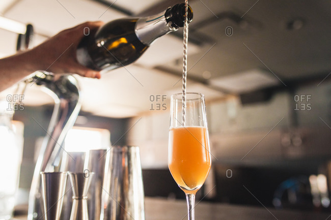 Hand pouring champagne into a flute