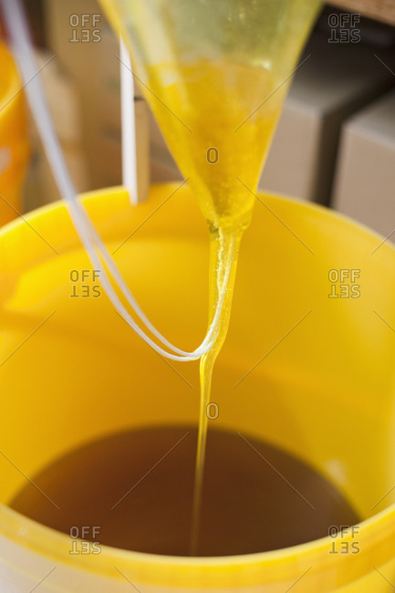 Close up of honey being poured in container