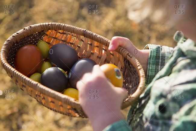 Midsection of child holding Easter eggs in basket outdoors