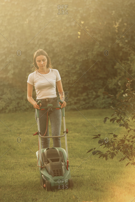 Woman trimming grass with lawn mower at yard