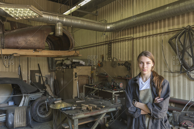 Portrait of confident female mechanic with arms crossed at repair shop