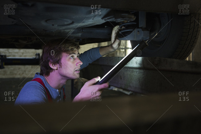 Mechanic with illuminated fluorescent light examining car from below