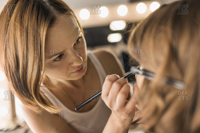 Artist applying make up on fashion model