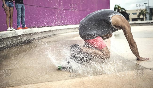 Young man bent over riding skateboard through water
