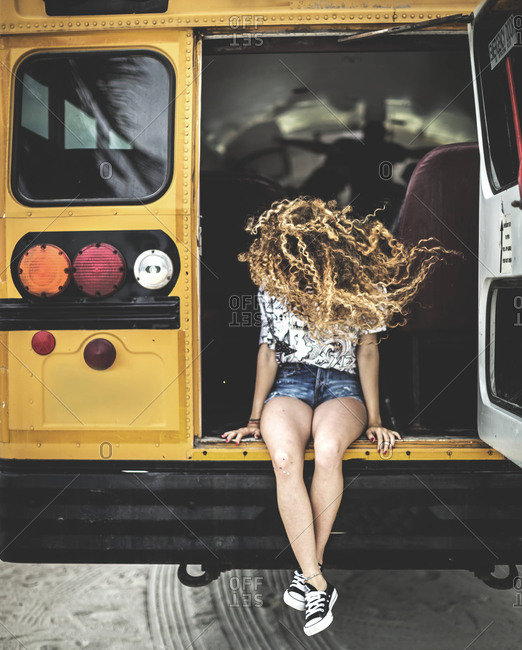 Portrait of young woman hanging out of the back of a school bus