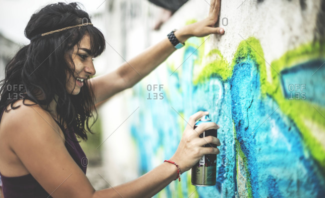 Young woman spray painting graffiti