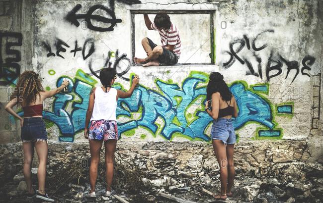 Group of teens spray painting graffiti