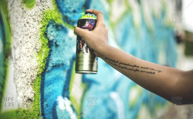 Close up of young woman spray painting graffiti