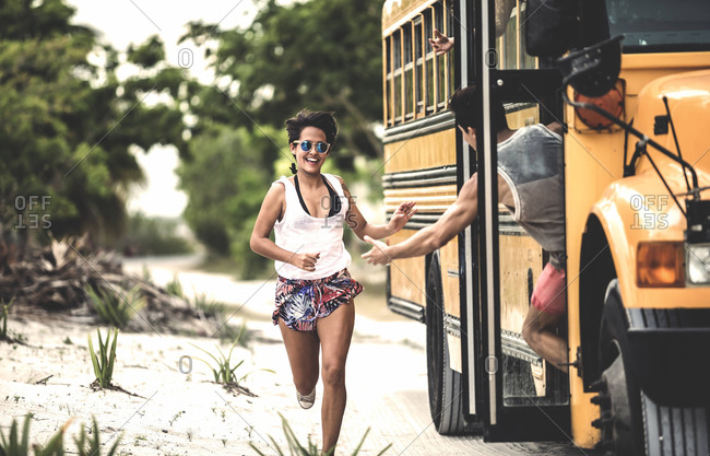 Young woman running to catch a school bus