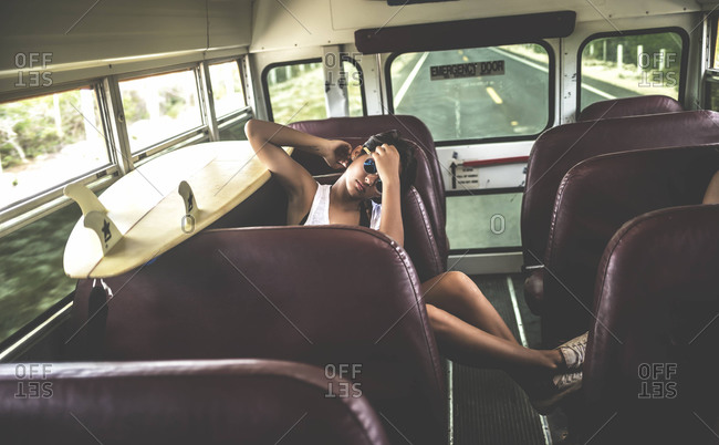 Young woman sitting with a surfboard on a school bus