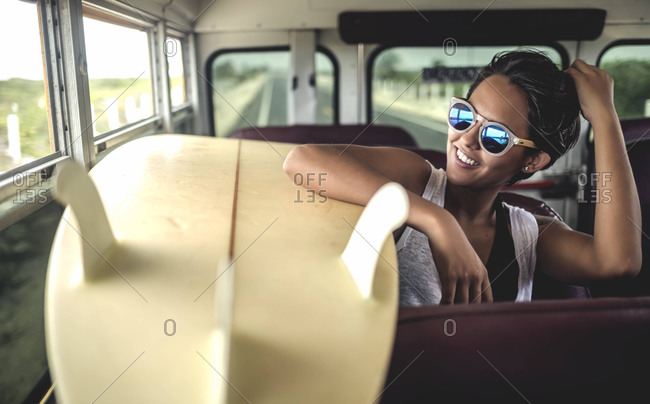 Young woman looking out window with a surfboard on a school bus