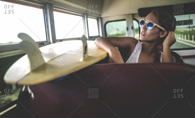 Young woman leaning on a surfboard on a school bus